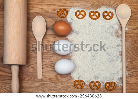 Wheat flour and eggs, a rolling pin and spoon on a wooden background. Top view. - stock photo