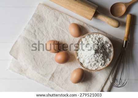 Wheat flour and eggs, a rolling pin, egg beater and spoon on a wooden background - stock photo