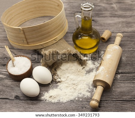 Wheat flour in a canvas bag,sieve, the olive oil in a glass carafe, a large salt shaker wood, raw eggs, a wooden rolling pin: set for making homemade bread dough on a beautiful dark wooden background. - stock photo