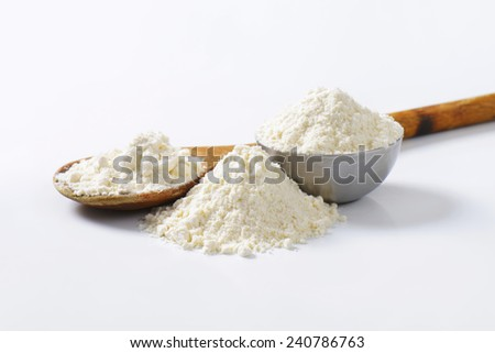 Wheat flour on wooden spoon and in metal bowl - stock photo