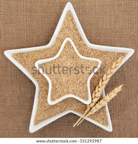Wheat Germ in star shaped white porcelain dishes with wheat sheath forming an abstract background. - stock photo