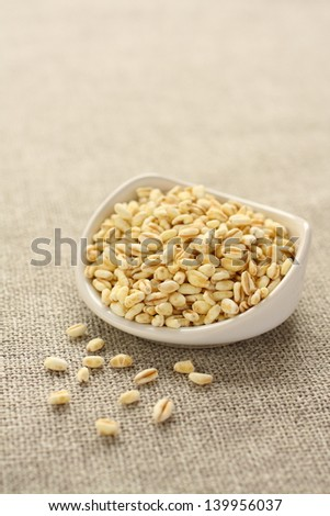 Wheat grains in white ceramic bowl on sackcloth background - stock photo