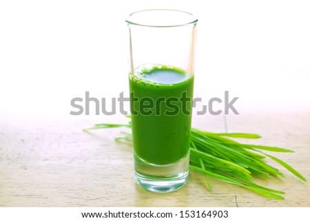 Wheat grass juice on wood background - stock photo