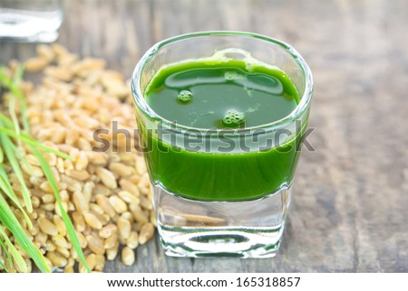 Wheat grass juice with fresh wheat grass and wheat on wood background  - stock photo