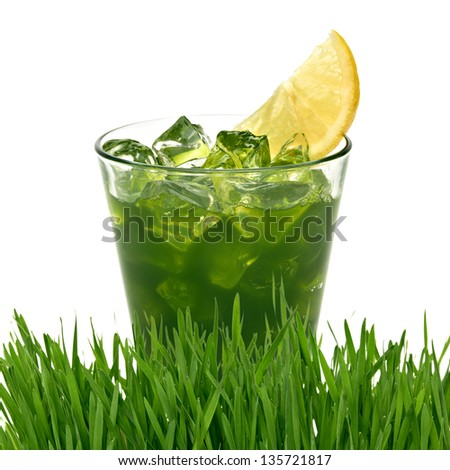 Wheat grass juice with lemon slice in glass on white background - stock photo