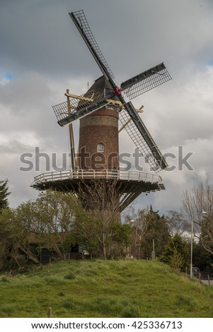 Wheat mill in Wolphaartsdijk, Netherlands during tempestuous spring weather - stock photo