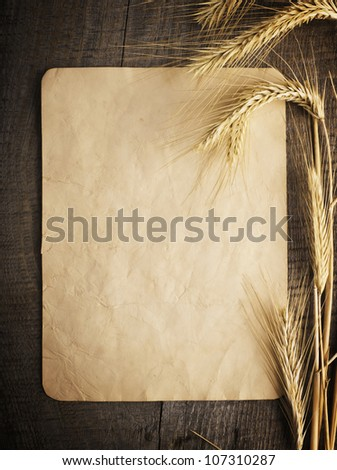 wheat on the old wooden table and old paper - stock photo