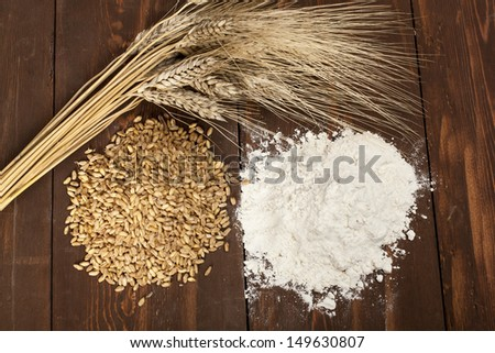 Wheat, plant seeds and flour on wooden table - stock photo