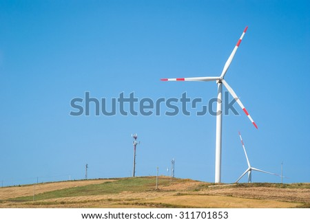 Wheatfield with windmills on blue sky - stock photo