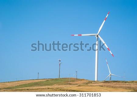 Wheatfield with windmills on blue sky - stock photo