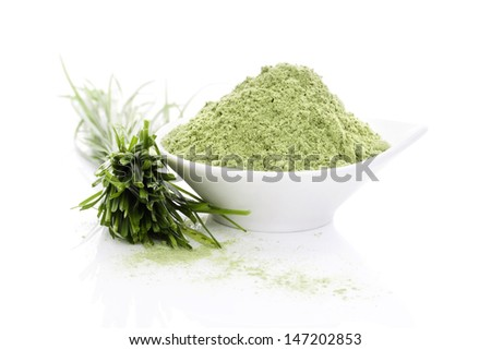Wheatgrass blades and barley grass ground powder isolated on white background with reflection. Natural organic healthy living. Superfood. - stock photo