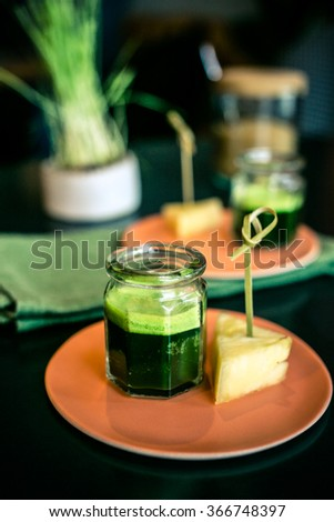 Wheatgrass juice with piece of pineapple on the plate in a restaurant, vertical - stock photo