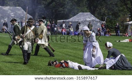 WHEATON, ILLINOIS/USA - SEPTEMBER 12, 2015: Two young women nurses attend to a fallen soldier while other combatants march by at a reenactment of the American Revolutionary War (1775-1783). - stock photo