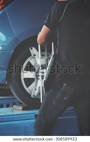 wheel alignment at repair service station - vintage style - stock photo