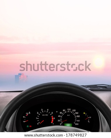 Wheel and dashboard of the car which going to the sunrise - stock photo