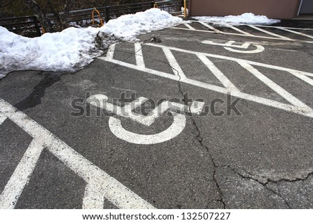 Wheel chair symbol in parking lot and snow in Japan - stock photo