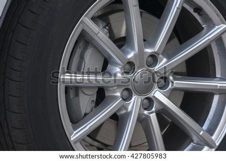 Wheel closeup with brake disc and caliper, alloy wheels - stock photo