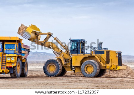 Wheel front-end loader unloading ore into heavy dump truck - stock photo
