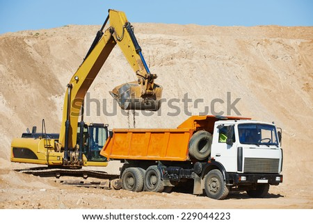 wheel loader excavator machine loading dumper truck at sand quarry - stock photo