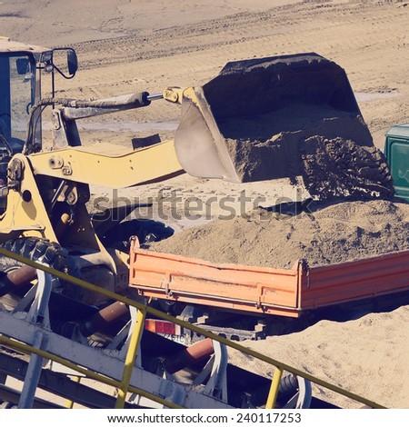 wheel loader excavator machine loading dumper truck at sand quarry - stock photo