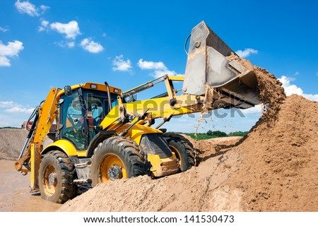 Wheel loader Excavator unloading sand with water during earth moving works at construction site - stock photo