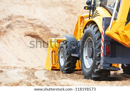 Wheel loader Excavator with backhoe unloading sand at eathmoving works in construction site quarry - stock photo