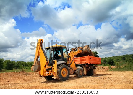 Wheel loader machine unloading soil to the dumper truck  in construction site. - stock photo