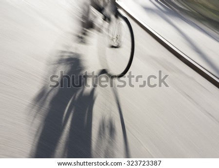 wheel of bicycle with shadow in blurred motion - stock photo