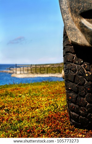 Wheel of offroad car against the  landscape of tundra coast - stock photo