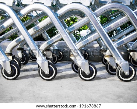 Wheel of shopping carts at parking lot - stock photo