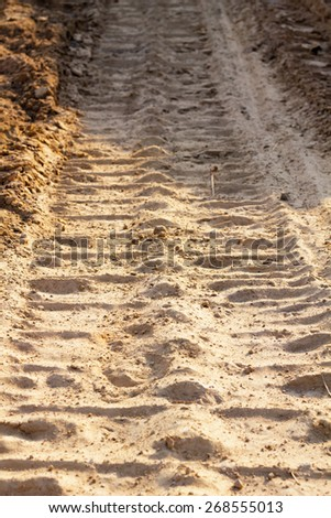 wheel track and foot print on clay road - stock photo