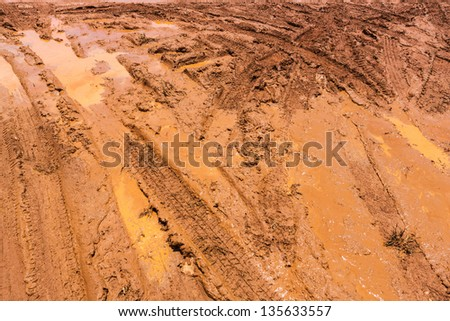 Wheel tracks on red color marshy road after raining - stock photo