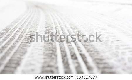 Wheel tracks on the winter road covered with snow. - stock photo