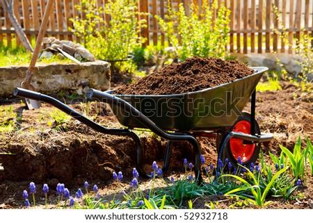 Wheelbarrow in a garden - stock photo