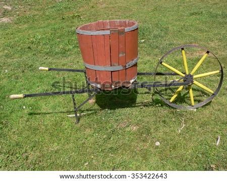 Wheelbarrow. Retro metal wheel with wooden barrel in the garden - stock photo