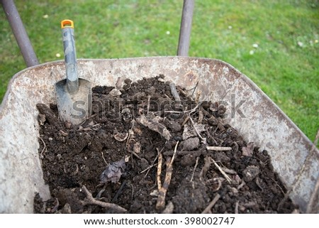 wheelbarrow with soil compost and a scoop - stock photo