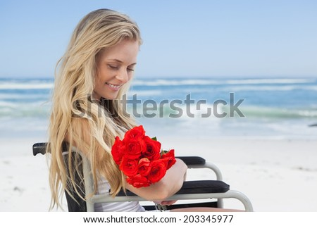 Wheelchair bound blonde smiling on the beach holding roses on a sunny day - stock photo