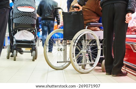 wheelchair bound invalid buyer in shopping center with assistant - stock photo