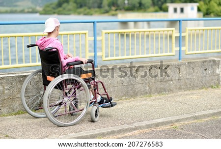 Wheelchair bound woman relaxing on the beach - stock photo