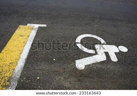 Wheelchair Handicap Sign on dark asphalt road street background- handicap parking place - stock photo