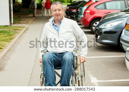 Wheelchair next to parking cars - stock photo