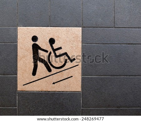 Wheelchair ramp. A sign of a person pushing a wheelchair with a person sitting on it. The sign is printed on a tile and paved on a wheelchair ramp. - stock photo