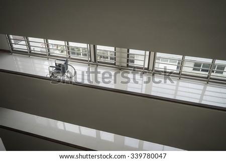 Wheelchair standing in an empty hospital corridor - stock photo