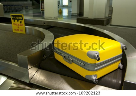 Wheeled luggage on airport conveyor belt - stock photo