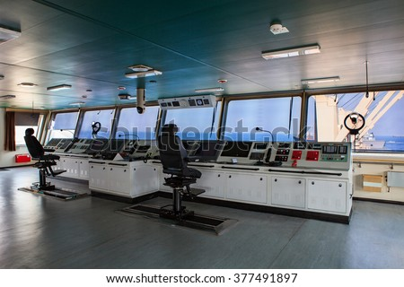 wheelhouse control board of modern industry ship approaching to harbor - stock photo
