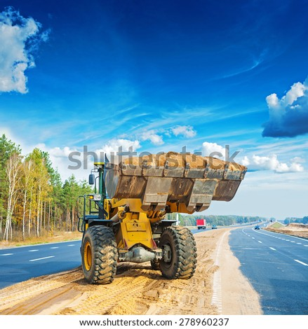 wheelloader with scoop full of sand construction concept - stock photo
