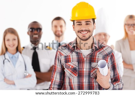 When I grow up I will be an engineer. Confident young man in hardhat holding blueprint and smiling while group of people in different professions standing in the background - stock photo