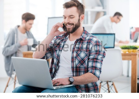 When the work is in full swing. Happy young man working on laptop and talking on the mobile phone while two people working in the background  - stock photo
