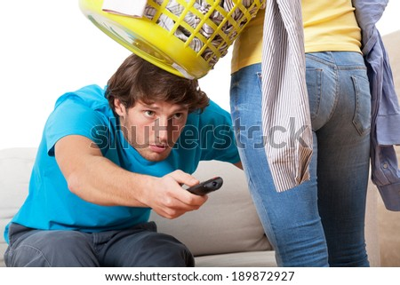 When woman cleaning flat, man is watching tv - stock photo