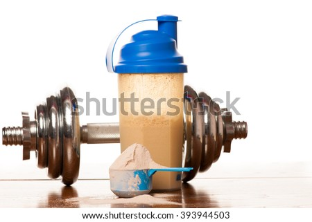 Whey protein powder in scoop, dumbbell, meter tape and plastic shaker on wooden background. - stock photo